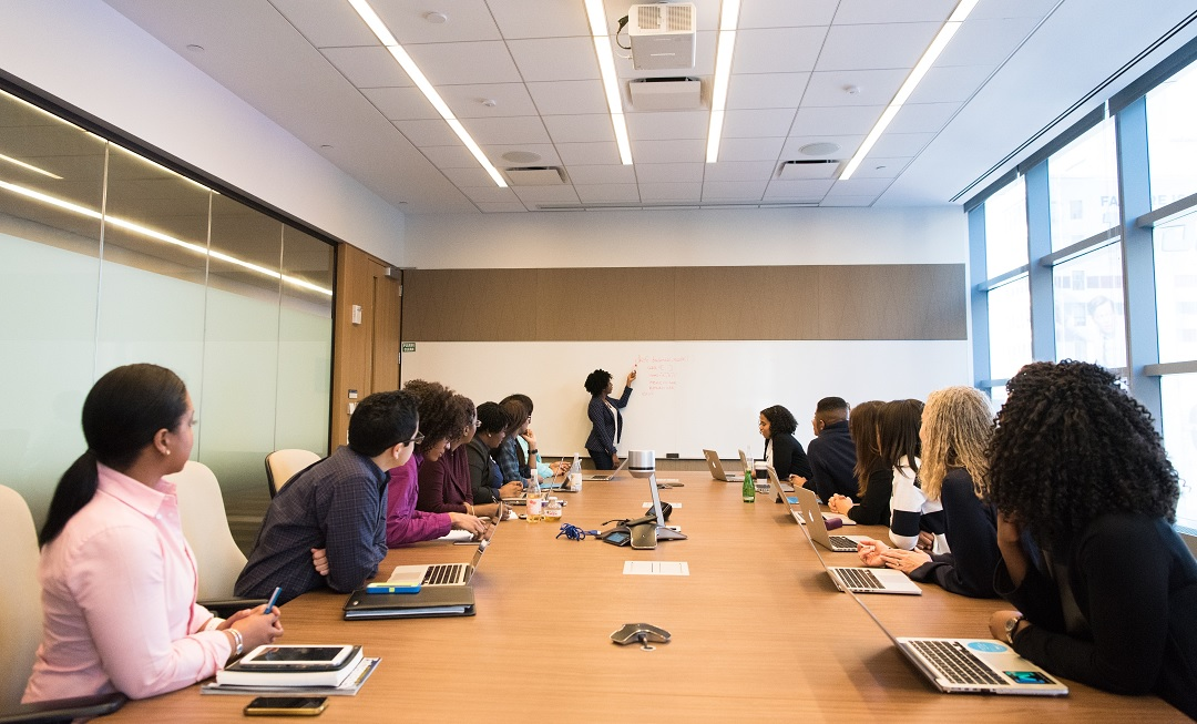 A group of people in a meeting boardroom watching a presenter